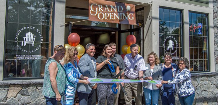 Adirondack Winery cuts the ribbon for their newest tasting room while surrounded by members of the Bolton Landing community