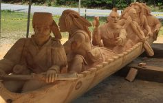 a large sculpture of Indians and a frontiersman in a canoe