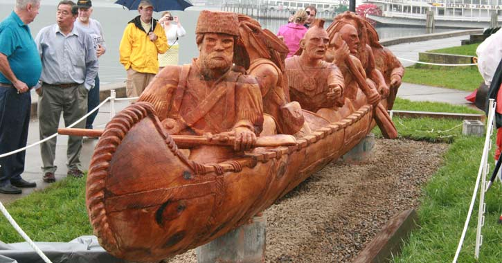 sculpture of Indians in canoe with people looking on