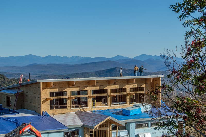 Workers atop the roof of the Saddle Lodge on Gore Mountain