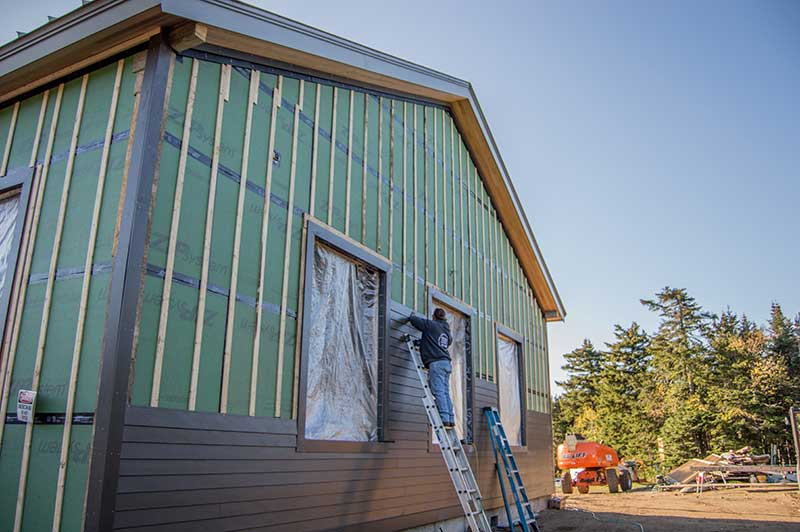 Construction worker installing hardie board siding on Straight Brook Lodge at Gore mountain's summit