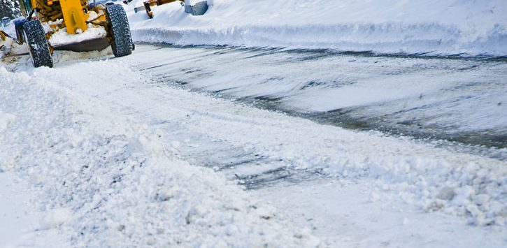 a road being plowed by a snowplow in the upper left corner of the photo