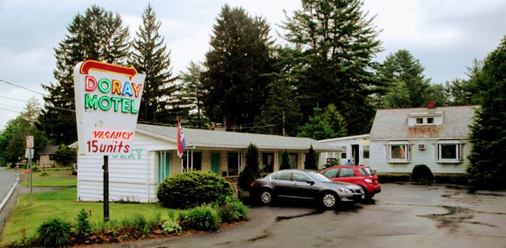 motel with cars out front and a sign saying Doray Motel