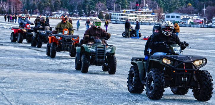 atv riders on a frozen lake