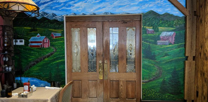 a mural of a field and sky surrounding a doorway