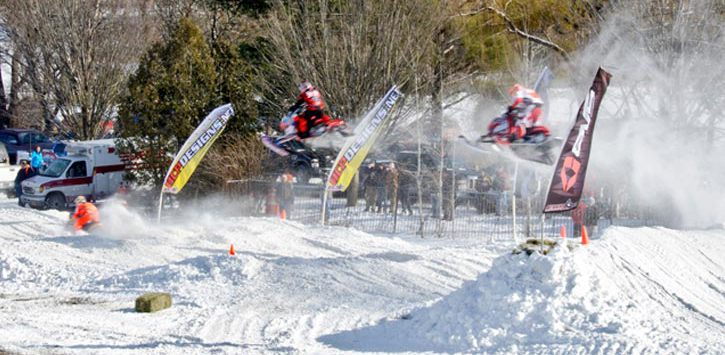 snowmobilers jumping over snow banks
