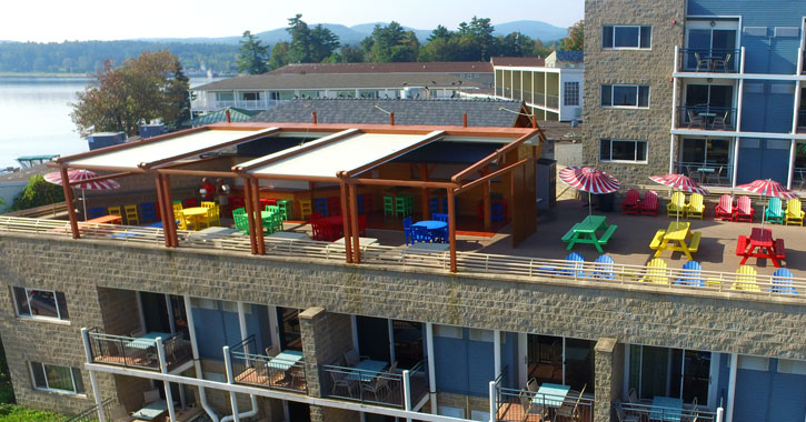 aerial view of a rooftop bar on motel with brightly colored chairs and tables