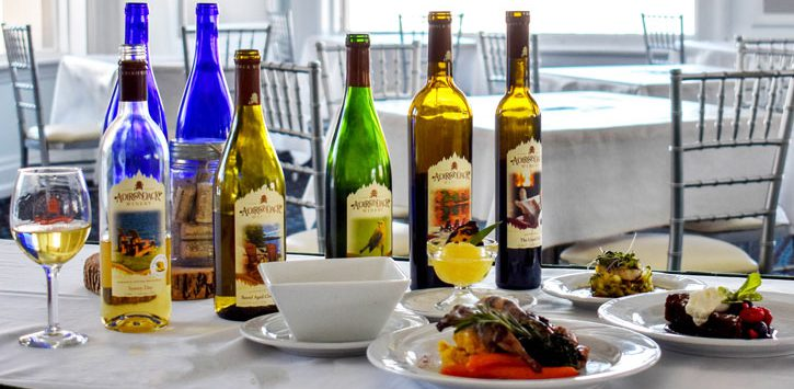 an elegant spread of food on a table with several bottles of Adirondack Winery wine