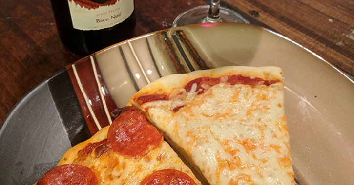 slices of cheese and pepperoni pizza with a bottle of wine behind them