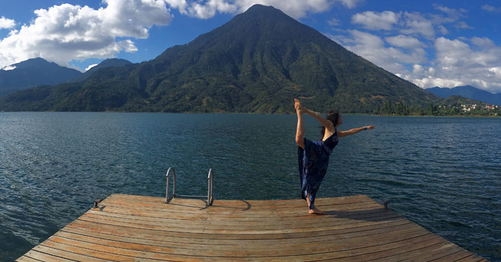woman in standing bow pose on a dock in front of the lake