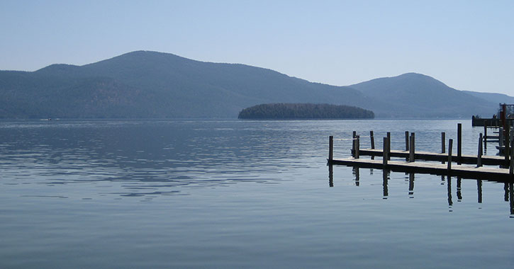 view of lake and mountains with dock to the side