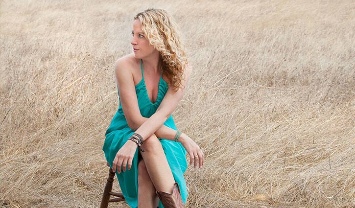 amy helm sitting on a stool in a field