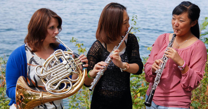 three women playing instruments by the water