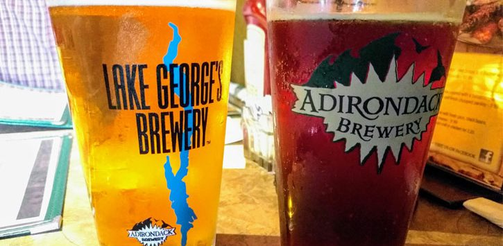 two glasses of beer in Lake George Brewery glass and Adirondack Brewery glass