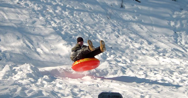 man snowtubing down a hill