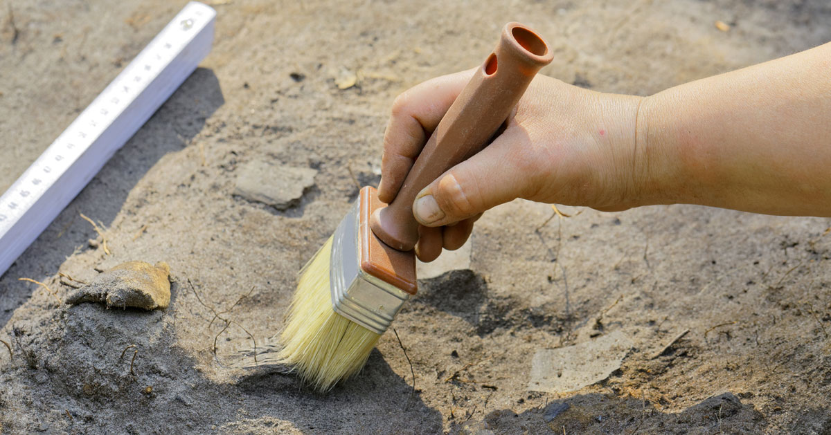 close up of hand brushing dirt at archaeology site