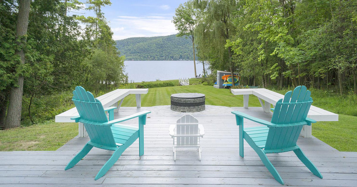 teal Adirondack chairs facing lake