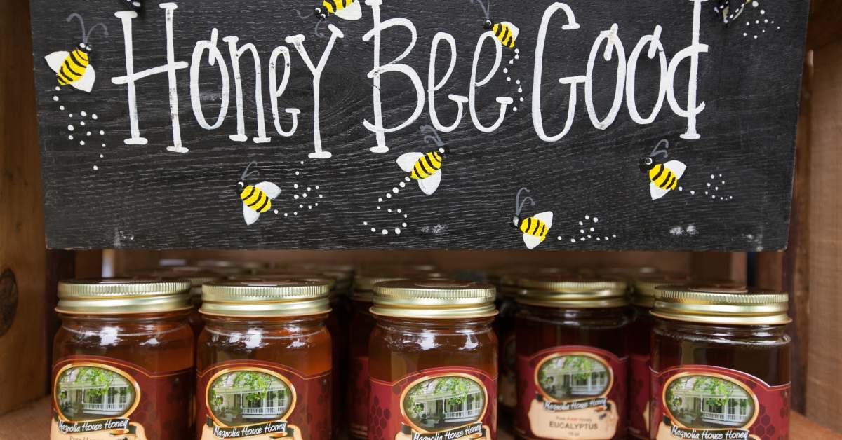 jars of honey with a sign that says honey bee good