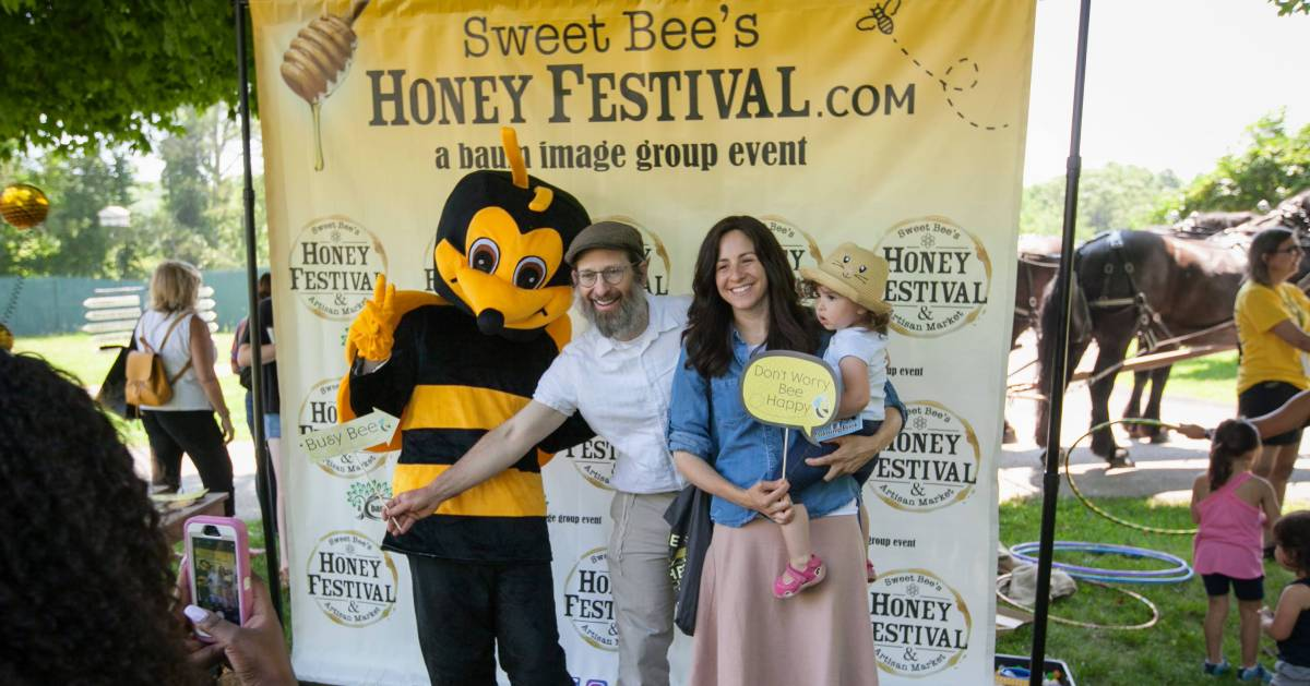 family posing with bee at Honey Festival