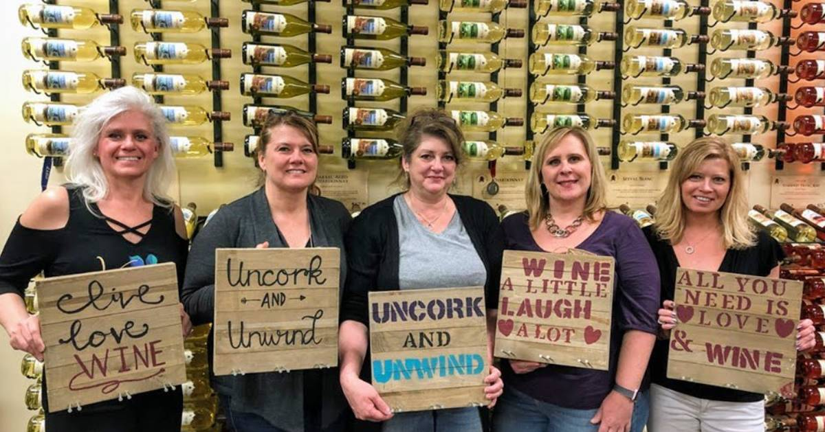 women holding up wine signs they painted