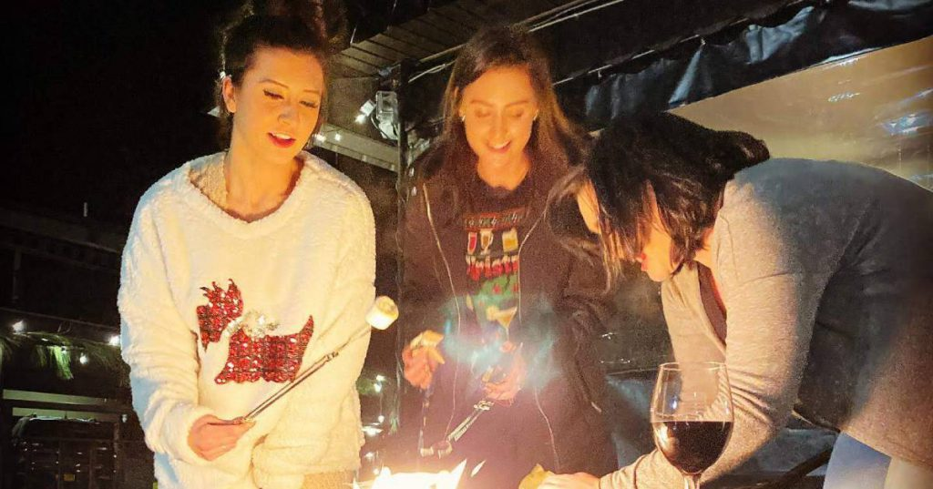 women around fire with s'mores