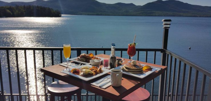food and drinks on outdoor table by lake