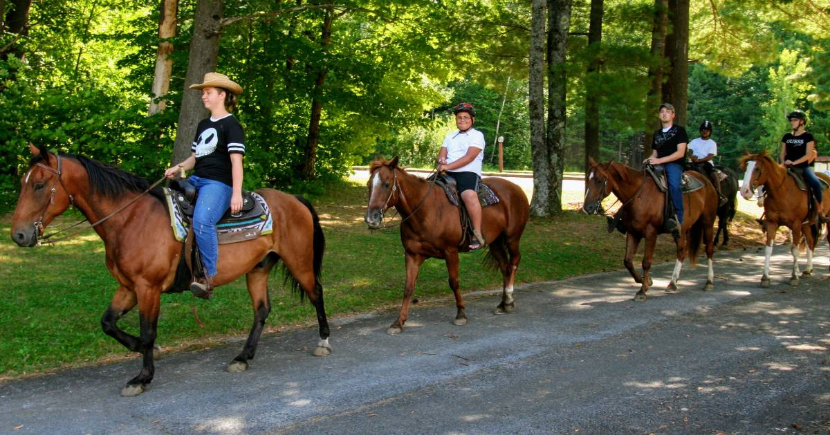 four people in a row on horseback