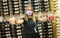 woman holding up wine slushies in front of wine wall
