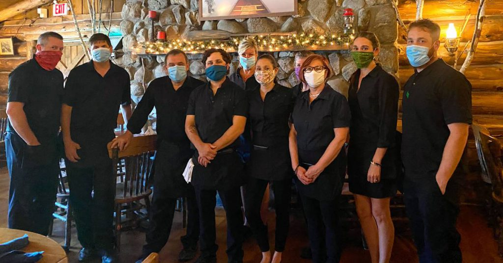 restaurant staff wearing masks in rustic dining room