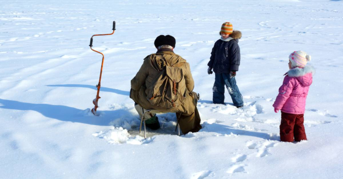man with kids ice fishing