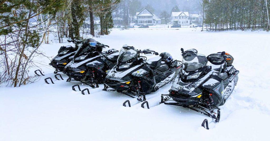four snowmobiles on snowy ground