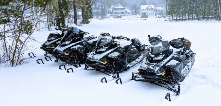 four snowmobiles on snowy ground
