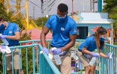three employees sanitizing ride area