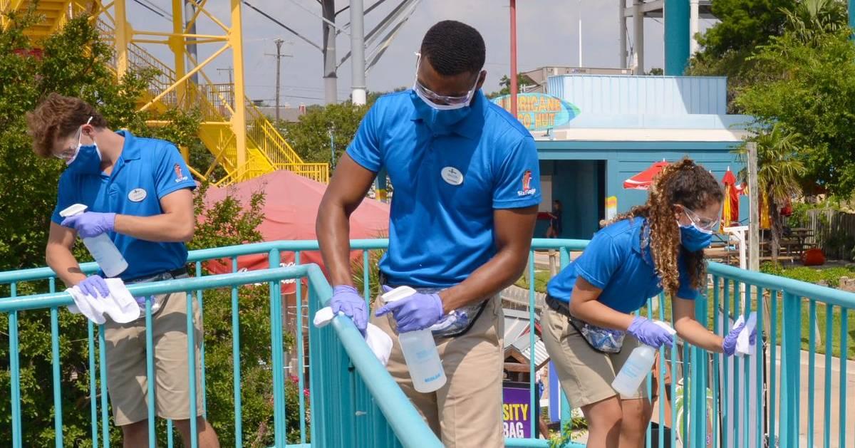 three employees sanitizing ride area