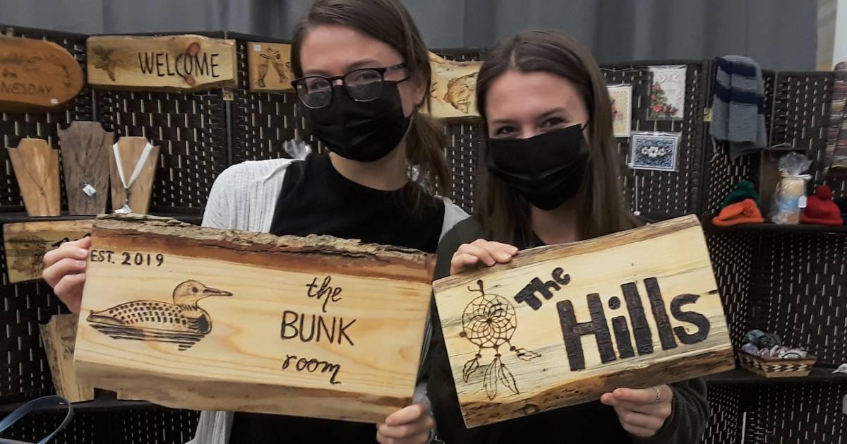 masked women holding up wood burning signs