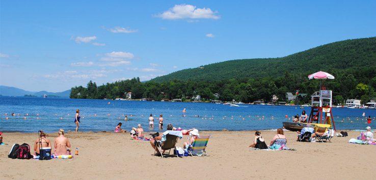 people swimming and sunbathing at million dollar beach on lake george