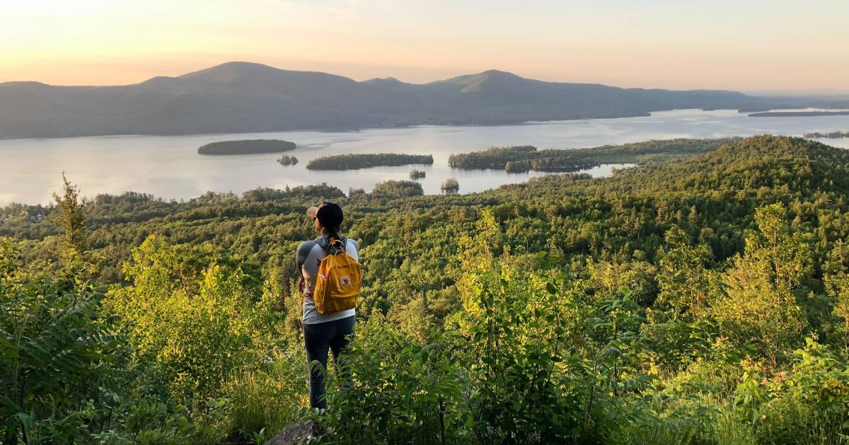 woman hiker looks at sunset